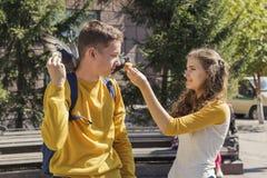 Adolescentes de los pares que alimentan palomas en la calle de la ciudad Imágenes de archivo libres de regalías