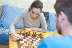 Adolescentes de los pares que juegan a ajedrez Fotos de archivo libres de regalías