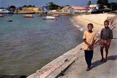 Adolescentes de piel morena de los africanos, 12 años, caminando a lo largo del mar Foto de archivo