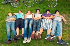 Adolescentes de reclinación después del paseo de la bicicleta Imágenes de archivo libres de regalías
