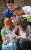 Adolescentes de risa que miran el panel táctil Imágenes de archivo libres de regalías