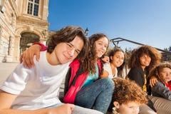 Adolescentes de risa que se sientan al aire libre en escalera Fotografía de archivo libre de regalías