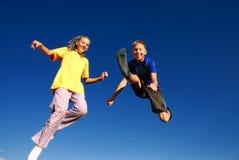Adolescentes de salto felizes   imagem de stock