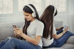 Adolescentes de soeurs avec le téléphone intelligent et la musique de écoute d'écouteurs et ommunicate dans les réseaux sociaux Photos libres de droits