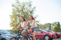 Adolescentes de sorriso que competem em bicicletas Imagem de Stock Royalty Free