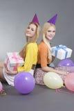 Adolescentes de sorriso que sentam-se com presentes e os balões coloridos Foto de Stock Royalty Free