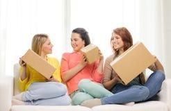 Adolescentes de sourire avec des boîtes en carton à la maison Photographie stock libre de droits
