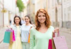 Adolescentes de sourire avec des paniers sur la rue Images stock