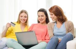 Adolescentes de sourire avec l'ordinateur portable et la carte de crédit Photographie stock