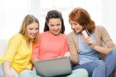 Adolescentes de sourire avec l'ordinateur portable et la carte de crédit Photographie stock libre de droits