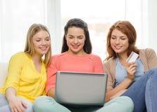 Adolescentes de sourire avec l'ordinateur portable et la carte de crédit Image libre de droits