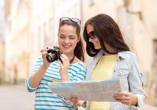 Adolescentes de sourire avec la carte et l'appareil-photo Photo stock