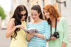 Adolescentes de sourire avec le guide et l'appareil-photo de ville Photographie stock libre de droits