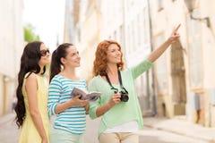 Adolescentes de sourire avec le guide et l'appareil-photo de ville Image libre de droits