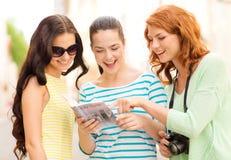 Adolescentes de sourire avec le guide et l'appareil-photo de ville Photos libres de droits