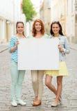 Adolescentes de sourire avec le panneau d'affichage vide Photo stock