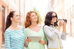 Adolescentes de sourire avec le PC et l'appareil-photo de comprimé Images stock