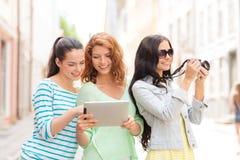 Adolescentes de sourire avec le PC et l'appareil-photo de comprimé Photos stock
