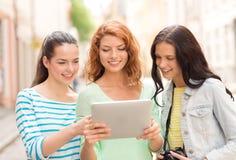 Adolescentes de sourire avec le PC et l'appareil-photo de comprimé Photos libres de droits