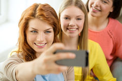 Adolescentes de sourire avec le smartphone à la maison Images libres de droits