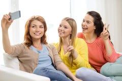 Adolescentes de sourire avec le smartphone à la maison Photos stock
