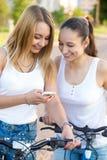 Adolescentes de sourire avec le téléphone portable Photo stock