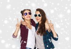 Adolescentes de sourire dans des lunettes de soleil montrant la paix Image stock