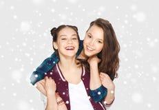 Adolescentes de sourire heureuses étreignant au-dessus de la neige Photos libres de droits