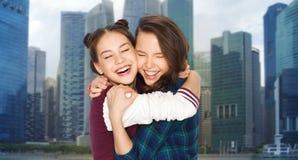 Adolescentes de sourire heureuses étreignant au-dessus de la ville Photographie stock