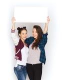 Adolescentes de sourire tenant le conseil vide blanc Photos stock