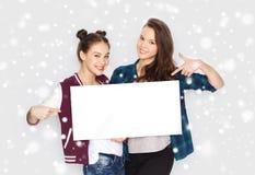 Adolescentes de sourire tenant le conseil vide blanc Images libres de droits