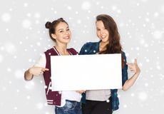 Adolescentes de sourire tenant le conseil vide blanc Images stock
