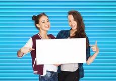 Adolescentes de sourire tenant le conseil vide blanc Photographie stock