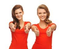 Adolescentes del Wo en las camisetas rojas que muestran los pulgares para arriba Foto de archivo