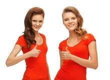 Adolescentes del Wo en las camisetas rojas que muestran los pulgares para arriba Fotos de archivo libres de regalías