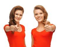 Adolescentes del Wo en las camisetas rojas que muestran los pulgares para arriba Fotografía de archivo