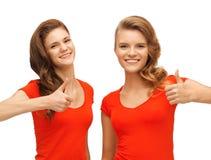 Adolescentes del Wo en las camisetas rojas que muestran los pulgares para arriba Imagenes de archivo
