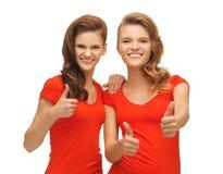 Adolescentes del Wo en las camisetas rojas que muestran los pulgares para arriba Imagen de archivo libre de regalías