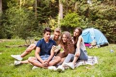 Adolescentes delante de la tienda que acampan en bosque Fotos de archivo libres de regalías