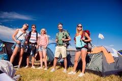 Adolescentes delante de las tiendas con las mochilas, festival del verano Imagen de archivo