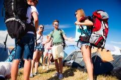 Adolescentes delante de las tiendas con las mochilas, festival del verano Fotografía de archivo