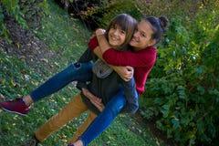 Adolescentes despreocupados que llevan a cuestas durante el día en el parque Imagen de archivo