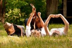 Adolescentes despreocupados que mienten en hierba Foto de archivo libre de regalías