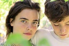 Adolescentes detrás de algunas hojas Foto de archivo libre de regalías