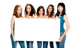 Adolescentes diversos con la muestra en blanco Imagen de archivo