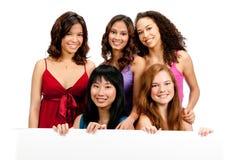 Adolescentes diversos con la muestra en blanco Foto de archivo