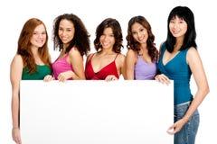 Adolescentes diversos con la muestra en blanco Fotografía de archivo
