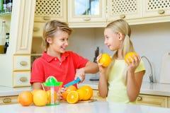 Adolescentes divertidos con la fruta cítrica Tenencia del muchacho y de la muchacha Imagenes de archivo