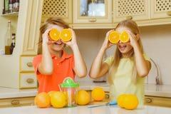 Adolescentes divertidos con la fruta cítrica Tenencia del muchacho y de la muchacha Foto de archivo libre de regalías