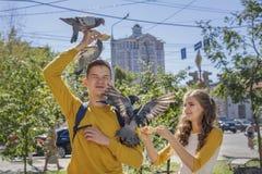 Adolescentes dos pares que alimentam pombos na rua da cidade Imagem de Stock Royalty Free